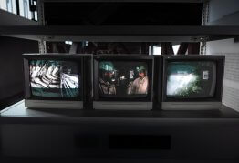three television screens are illuminated on a shelf in a dark room, each showing a different image/channel