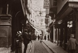 a black and white photo of a high street. the street is narrow and there is a cathedral in the background