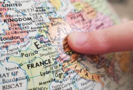 a finger points to Germany on a map of Europe