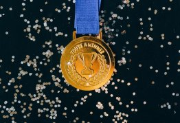 """a gold medal featuring the words """"you're a winner"""" lies on a black, glittery background"""