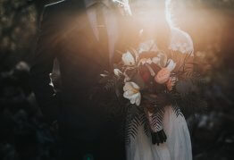 a newly married couple in the late evening sun, with a bouquet of orange and white flowers