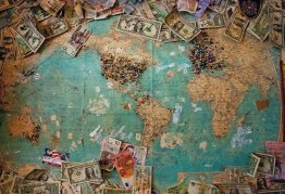 a world map surrounded by paper money