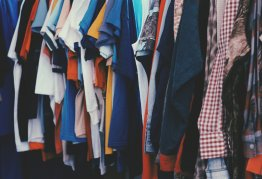 tshirts and tops hung up neatly on a clothes rail in assorted bright colours