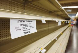 an empty supermarket shelf with a note attached asking customers not to panic buy basic items