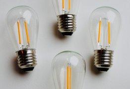 four lightbulbs laid against a white wall