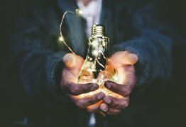 ink covered clasped hands hold an illuminated light bulb