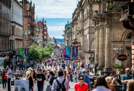 a busy glasgow highstreet full of people and shops, the sun shines in the background