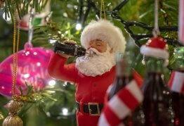 a christmas ornament of santa claus drinking coca cola