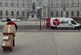 a DPD delivery man wheels boxes with his van in the background