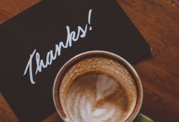 a card that says thanks is tucked under a cup of coffee on a coffee table