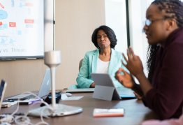 two women sat around a conference table in discussion. laptops and phones on the table