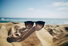 a pair of RayBan sunglasses resting on a sandy beach on a warm, sunny day