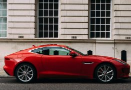 a small, red sports car sits parked on the side of a london road, a nice building behind it