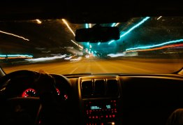 a car drives at night. the lights along the road blur to become solid lines