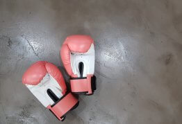 a pair of pink boxing gloves lie on a stone floor