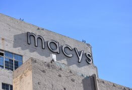 a white brick building with a big macy's store sign on the front