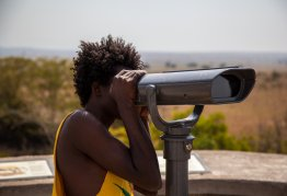 a man uses coin operated binoculars to look into the distance