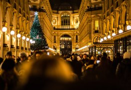 shoppers fill an old-fashioned street at night with a christmas free in the background