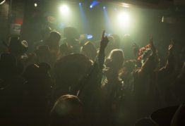 a large group of people in cowboy hats dance in a darkened room, party lights around them, and arms raised in the air