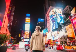 a man stands in the middle of a brightly lit Times Square at night
