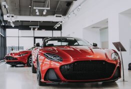 two red sports cars inside a car dealership building
