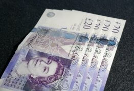 twenty pound notes fanned out on a grey tabletop