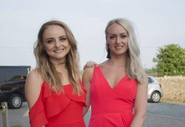 two girls in red party dresses smile happily towards the camera as they enter an event