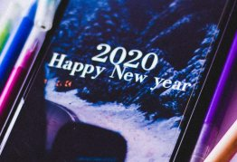a smartphone screen says happy new year 2020, surouded by coloured crayons