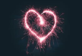 a bright pink sparkler used to trace a heart shape in the night sky