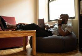 a man reclines on a beanbag whilst working on a laptop