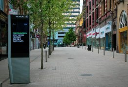 """a deserted high street with all the shops closed. A sign near the forefront reads """"coronavirus. stay home, protect the nhs, save lives."""""""