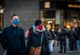 two people walking near shops wearing face masks