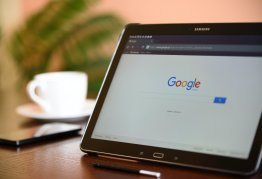 a tablet open to the google search bar rests on a table next to a cup of coffee