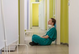 a nurse wearing scrubs sits alone in an empty hospital corridor, tired and run down.