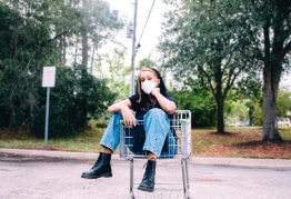 a girl in a covid mask sits in a shopping trolley in an empty car park