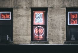 """three dark, black windows with neon signs that say """"psychic"""" and """"tarot cards"""""""