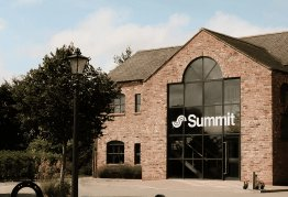 The Hull Summit office stands against a bright blue sky, the Summit logo displayed largely on the front window in white