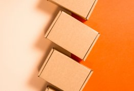 3 small, letterbox sized cardboard boxes sit flat on a bright orange background