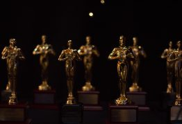 two rows of gold statues stand against a black background