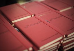 """lots of stacks of red notebooks stamped with the word """"Summit"""""""