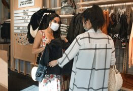 two women wear masks whilst shopping for clothes