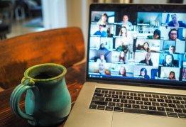 a mug sits next to an open laptop displaying zoom