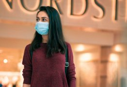a women stands in from of nordstrom wearing a mask