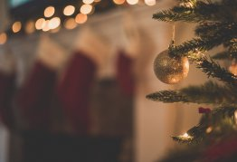 a gold christmas bauble hangs on a christmas tree