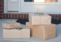 a stack of nicely wrapped christmas presents sit in front of a front door