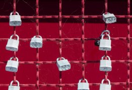 lots of padlocks on a bright red chain fence