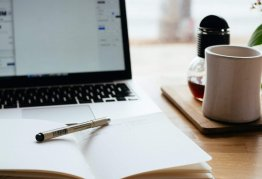 an open notebook sits in front of a turned on laptop and a cup of coffee