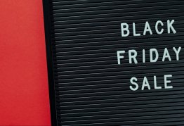 """a black letter board sits on a red background with the words """"black friday sale"""" displayed"""