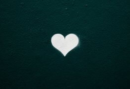 a spray painted white heart on a dark concrete wall