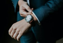 a man pulls his suit jacket sleeve over his expensive watch